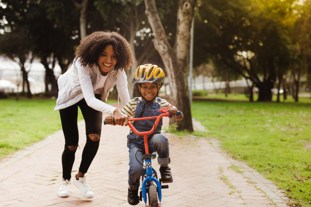 Mother teaching son to ride a bike in Shelburne