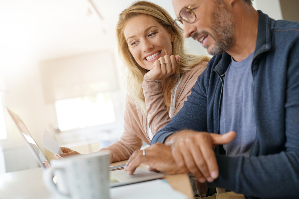 Couple buying a home on a laptop